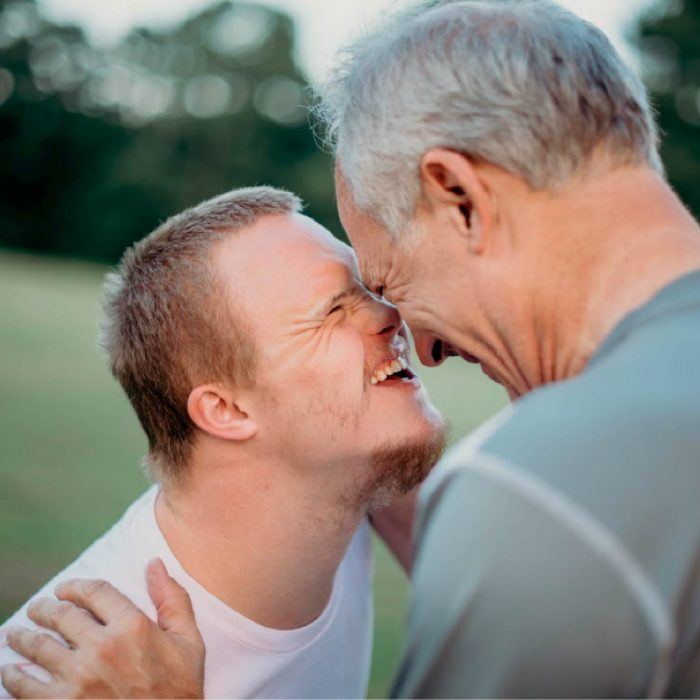 Laughing young man embracing happy older father