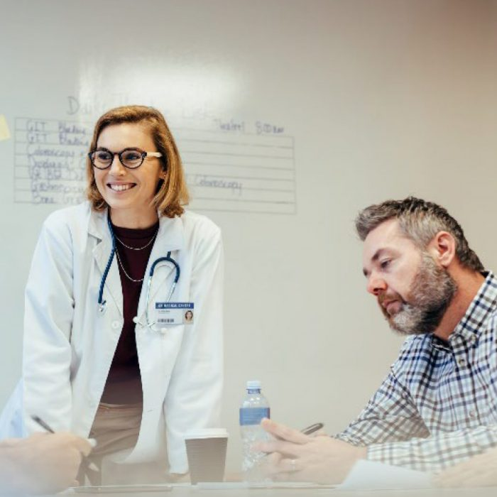 Doctor Wearing White Coat in meeting with colleagues